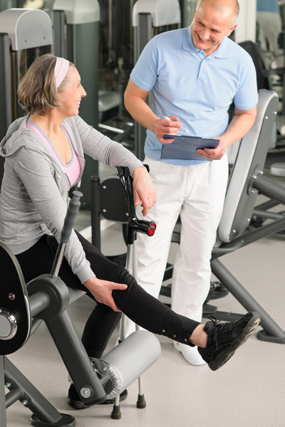 Physical therapist male assist active senior woman exercise at g